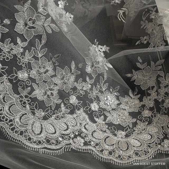 Blumen Spitze auf Tüll in Weiß mit Mini Pailletten in Silber.