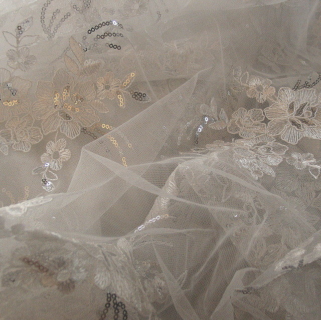 Blumen Spitze auf Tüll in Weiß mit Mini Pailletten in Silber.   Ansicht: Blumen Spitze auf Tüll in cremiges fast Weiß.