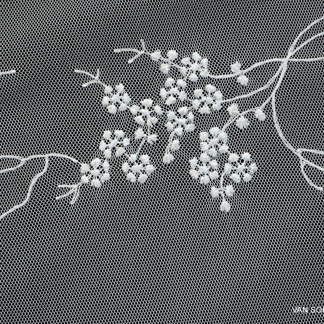 Fluttering fine mini flowers in white on tone in tone white tulle