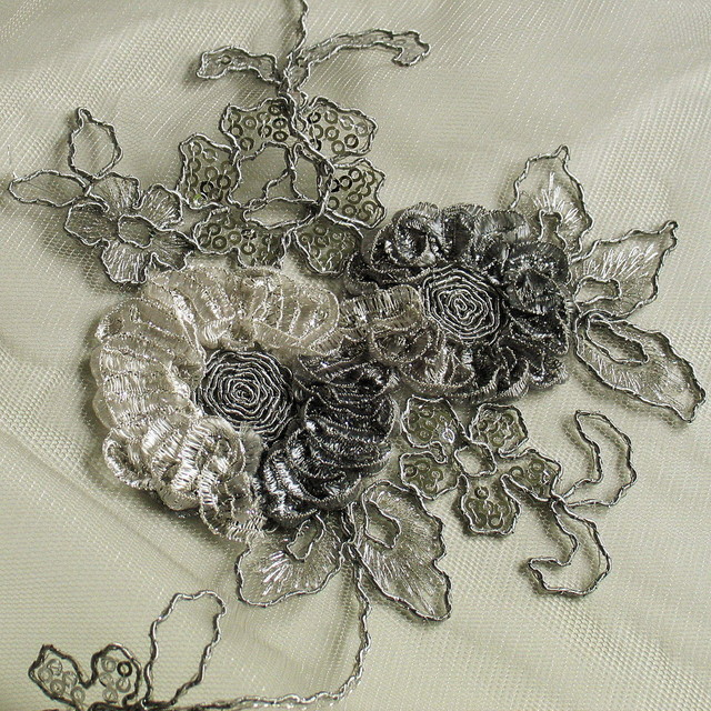 Silver coloured flower lace on grey coloured mesh