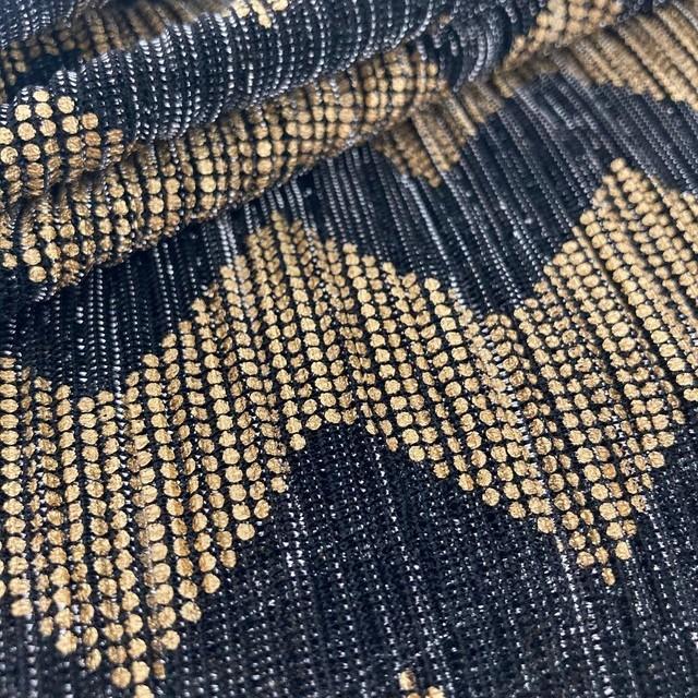 Zackenmuster bedruckt in Gold auf einem schwaz-silber-durchsichtigen Stretch Mikroplissee